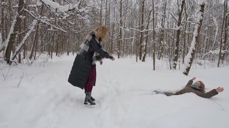 rodzeństwo : two happy adult female siblings are playing in snowy forest in winter day, one is pushing other Wideo