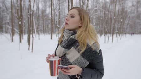 ona : young blonde woman is strolling alone in winter forest in daytime, she is holding coffee and phone Dostupné videozáznamy