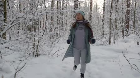 az érintett : scared adult woman is fleeing in winter forest in daytime, looking back, she is tired, stopping Stock mozgókép