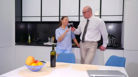 posiłek : businessman and housewife are drinking red wine in kitchen in evening time