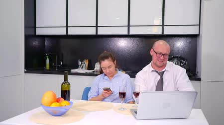 resimlerinde : cheerful married couple are sitting on kitchen with smartphone and laptop, they are smiling