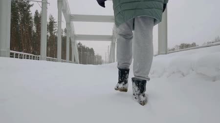 material body : lonely woman is walking over path covered snow in winter day, moving to contemporary bridge