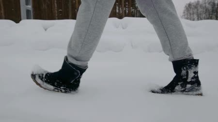 passer by : man or woman is strolling over snow in winter day, close-up view of shoes Stock Footage