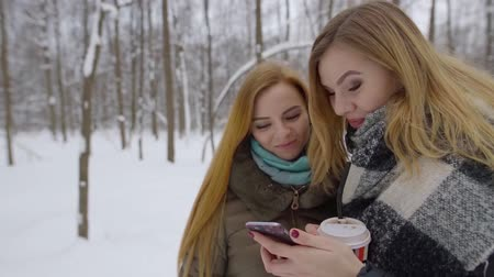 sending : pretty young woman is showing funny video to her female friend using mobile phone, standing in snowy forest