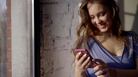 gumka : beautiful girl standing at the window, smiling and looking at the smartphone.