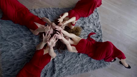 bohyně : Four female models lie on the floor on the carpet in red beautiful dresses and move their hands, palms up, relax, enjoy life
