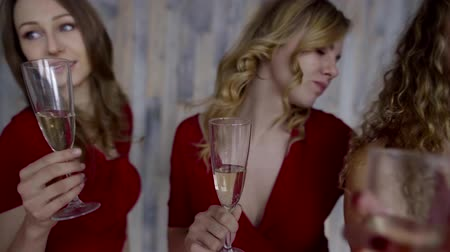 air kiss : four girls in red dresses hanging out at a party with glasses of wine Stock Footage