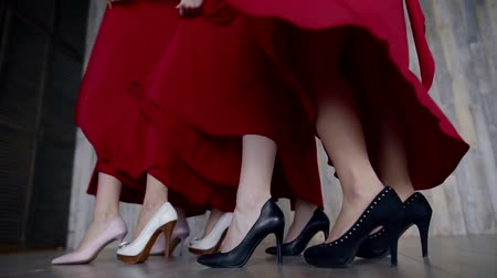 black and white : legs of four girls in high heels, red dresses develop