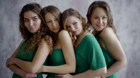 identical : four beautiful smiling models in the same green dresses stand and pose Stock Footage