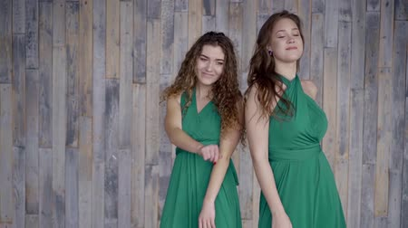 identical : two beautiful girls with dark hair in green dresses move, enjoy life, dance indoors