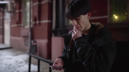 ужасный : asian male adolescent is smoking in street in evening and reading sms on smartphone