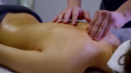 sobre : professional massagist is stroking back of female client in salon, performing cure for spine Stock Footage