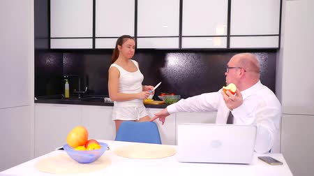 esvoaçantes : middle aged businessman is talking with his wife cooking dinner in evening after work, sit on kitchen Stock Footage