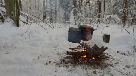 konvice : firewood are burning inside large campfire, three black pots are hanging over in snowy forest in winter day