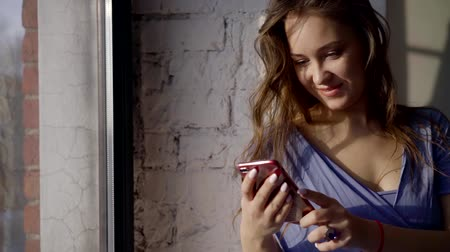 cotidiano : beautiful girl standing at the window, smiling and looking at the smartphone.