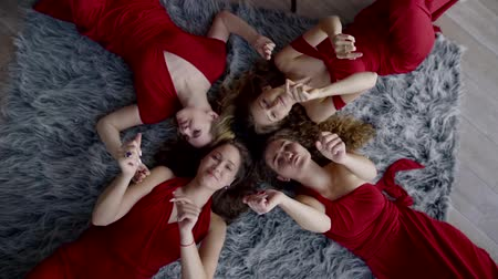 each other : four girls in identical red dresses, lying on the carpet dancing, moving their hands, their hair intertwined with each other Stock Footage