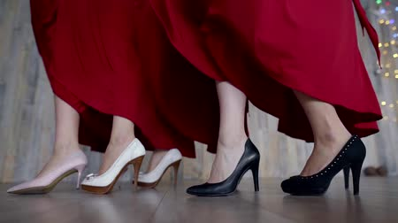 vysoký : legs of four girls in high heels, red dresses develop