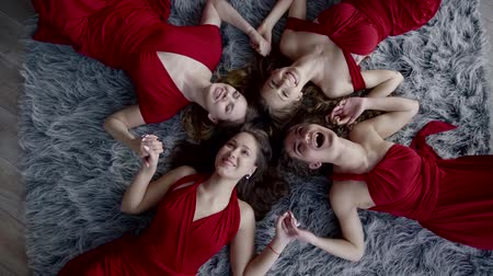 group people : four funny women are lying on floor, holding hands, looking at camera and screaming cheerfully