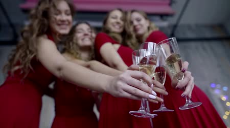 desfocado : four cheerful girls are holding goblets with champagne in front of camera