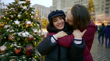 caresses : young bearded man is hugging and kissing his girlfriend, standing on square with christmas tree
