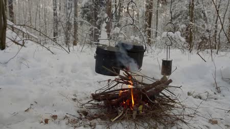 fat burning : Three pots with soup hanging above the fire in a winter forest, little picnic outdoor. Stock Footage
