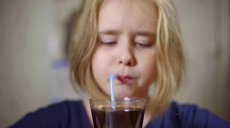 karbonatlı : Close-up shot of a cute little girl with drinking coke from a glass. Stok Video