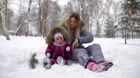 den matek : Mother playing with hed cute daughter sitting in a snowbank in a park, beautiful winter season.