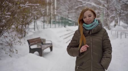 don : Charming blonde girl peacefully walking in a city park in in beautiful wintetime.