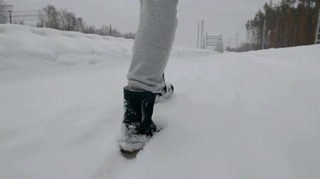 footgear : Legs of a woman in winter boots walking through the forest, lots of snow in nature.
