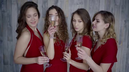 bachelorette party : Four amazing young girls posing with champagne glasses, toasting and smiling,