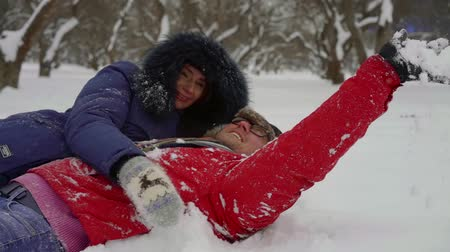 в середине : Happy and beautiful childish couple lying in snow and enjoying the day, playful couple. Стоковые видеозаписи