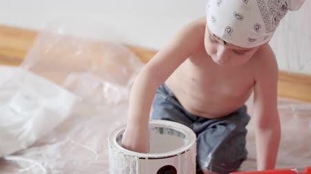 parede : little cute boy kid dunks finger in paint can painting wall at home