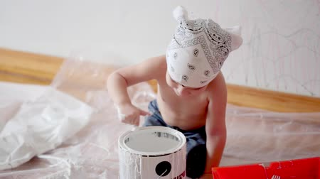 натюрморт : little cute boy kid dunks finger in paint can painting wall at home