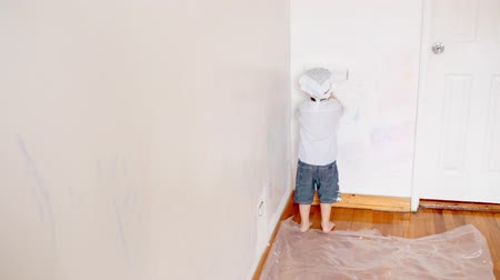 натюрморт : little boy kid painting the white wall at home. Decorating new apartment. Стоковые видеозаписи