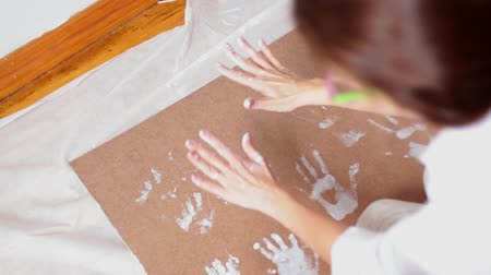 интимный : A little cute happy funny child painting white handprints with mother together