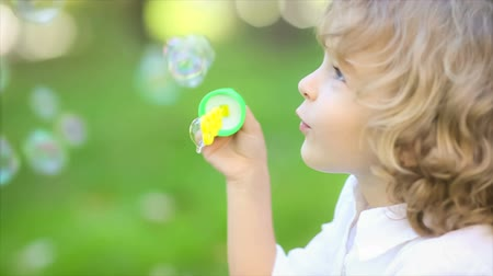 Happy child blowing soap bubbles in spring park. Slow motion