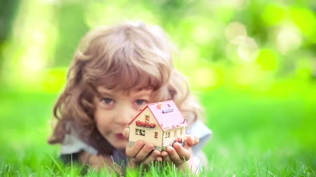 tavasz : Happy child holding model house in spring park. Slow motion