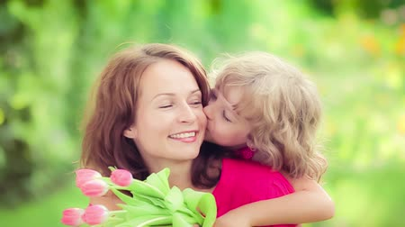 mother love : Beautiful child kissing young woman in spring park. Mothers day holiday concept Stock Footage