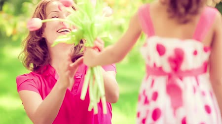 dát : Child giving flowers to the young woman in spring park. Mothers day holiday concept