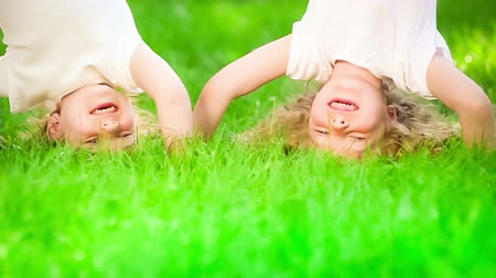 Happy children having fun in spring park. Funny kids standing upside down on green grass. Healthy lifestyle concept