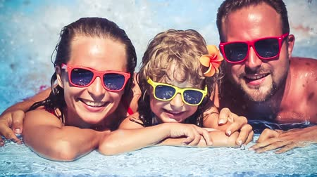 happy holidays : Happy family having fun in swimming pool. Summer vacations concept. Slow motion Stock Footage