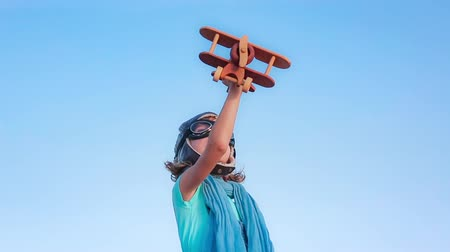 sen : Happy child playing with toy airplane against summer sky background. Slow motion