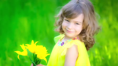 bouquets : Happy child with bouquet of flowers against green background. Spring family holiday concept. Mothers day. Slow motion Stock Footage