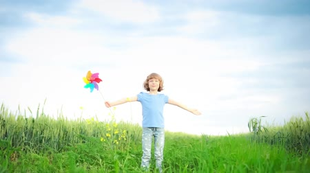 Happy child playing outdoors in spring field. Slow motion 影像素材