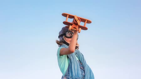 sen : Happy child playing with toy airplane against summer sky background