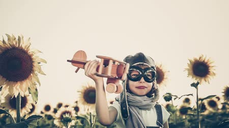 Happy child playing with toy airplane in spring sunflower field. Slow motion. Retro toned