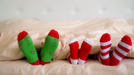 sock : Family in Christmas socks in bed. Mother; father and baby having fun together. People relaxing at home. Winter holiday Xmas and New Year concept Stock Footage