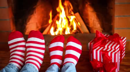 Couple in Christmas socks near fireplace. Man and woman having fun together. People relaxing at home. Winter holiday Xmas and New Year concept