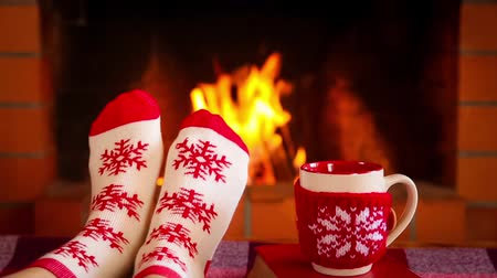 Womens feet in Xmas socks against fireplace