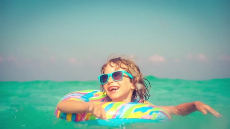 Happy child playing in the sea. Girl having fun outdoors. Summer vacation and holiday concept. Slow motion